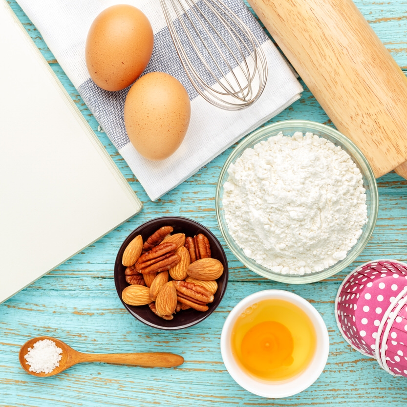 Bake background with baking ingredients and notebook on wood table