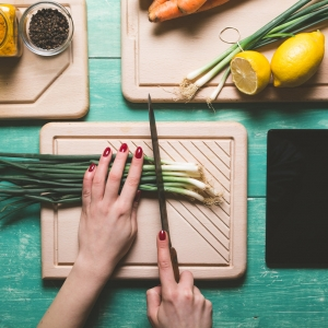 Female person cutting fresh spring onion on a blue wooden table. View from above.