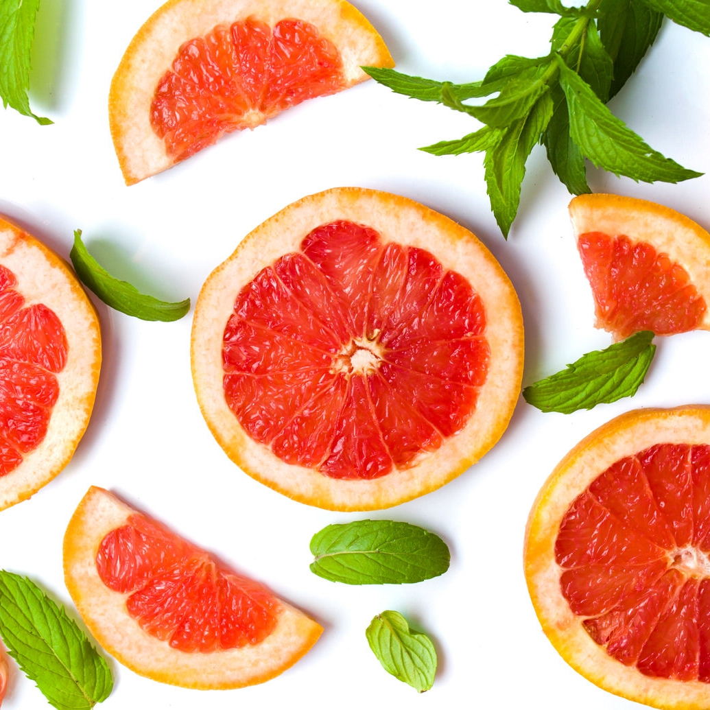 Grapefruit slices and mint leaves isolated on white