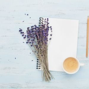 Morning cup of coffee, clean notebook and lavender flower on blue background top view. Woman working desk. Cozy breakfast. Flat lay style.
